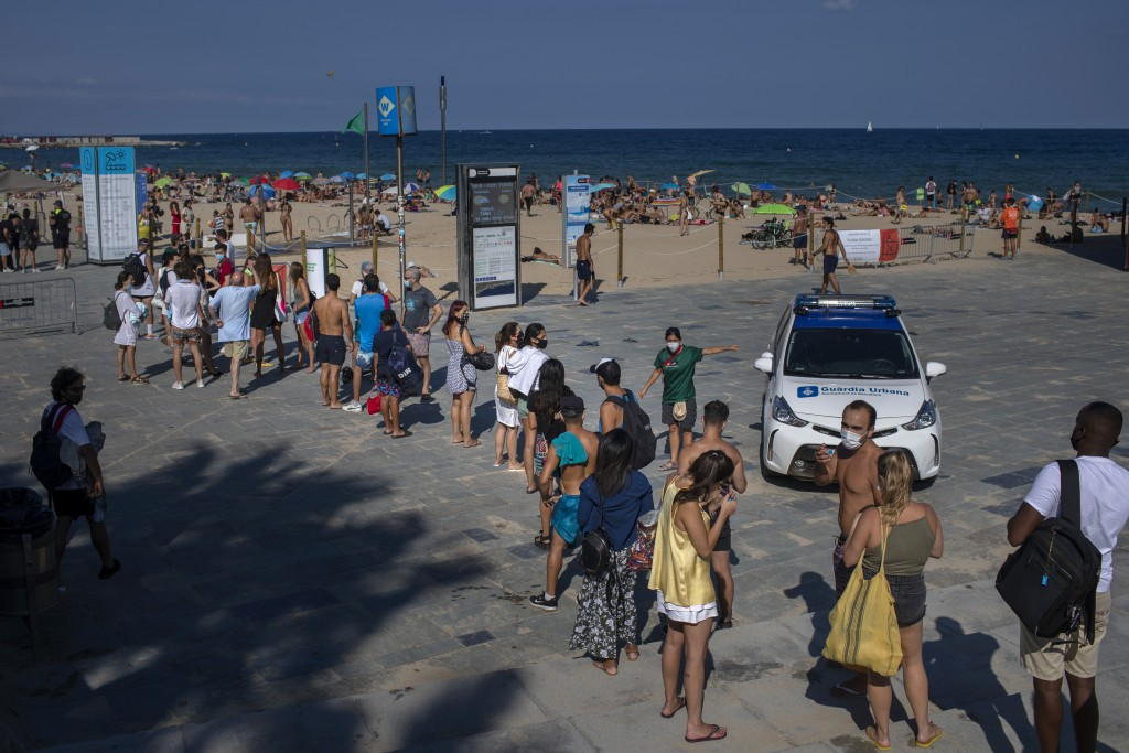 People wait to enter a beach that was closed by police due to crowding in Barcelona, Spain, Saturday, July 18, 2020. Police in Barcelona are closing a...