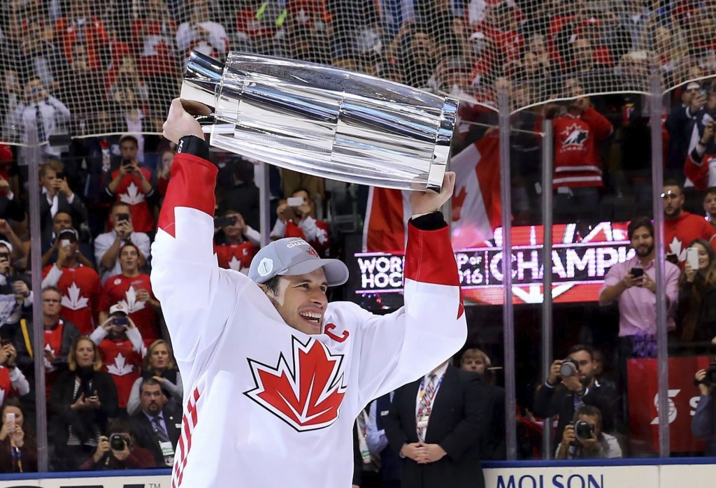 FILE - In this Sept. 29, 2016 file photo, Canada's Sidney Crosby hoists the trophy following his team's victory over Europe in the World Cup of Hockey...