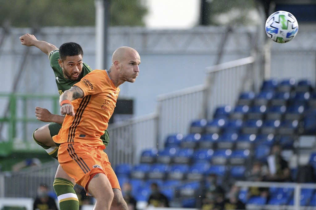 Portland Timbers defender Bill Tuiloma, left, and Houston Dynamo defender Aljaz Struna compete for a header in front of the goal during the first half...
