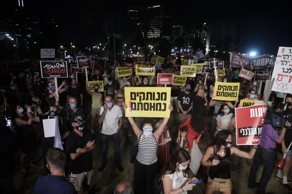"""Israelis hold signs during a protest In Tel Aviv, Israel, Saturday, July 18, 2020. The sign says in Hebrew reads:""""Out if touch, we are fed up."""" (AP Ph..."""
