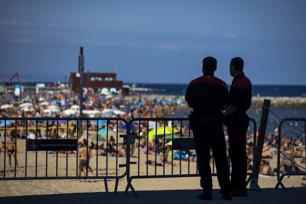 Police officers guard a barrier to stop people entering the beach, in Barcelona, Spain, Saturday, July 18, 2020. Police in Barcelona are closing acces...