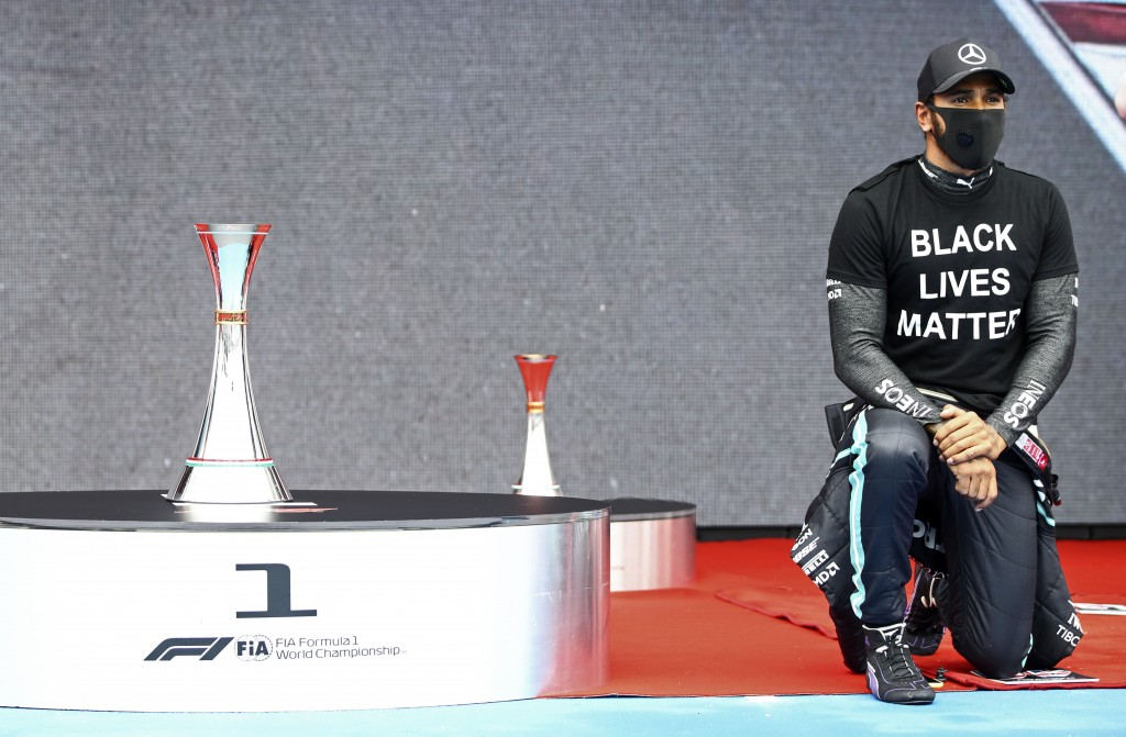 Mercedes driver Lewis Hamilton of Britain takes the knee beside the trophy prior the the Hungarian Formula One Grand Prix race at the Hungaroring race...