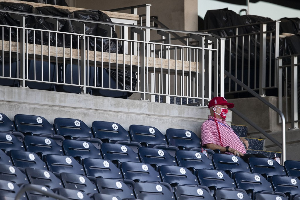 Washington Nationals owner Mark Lerner wears a face mask as he sits in the stands during an exhibition baseball game against the Philadelphia Phillies...