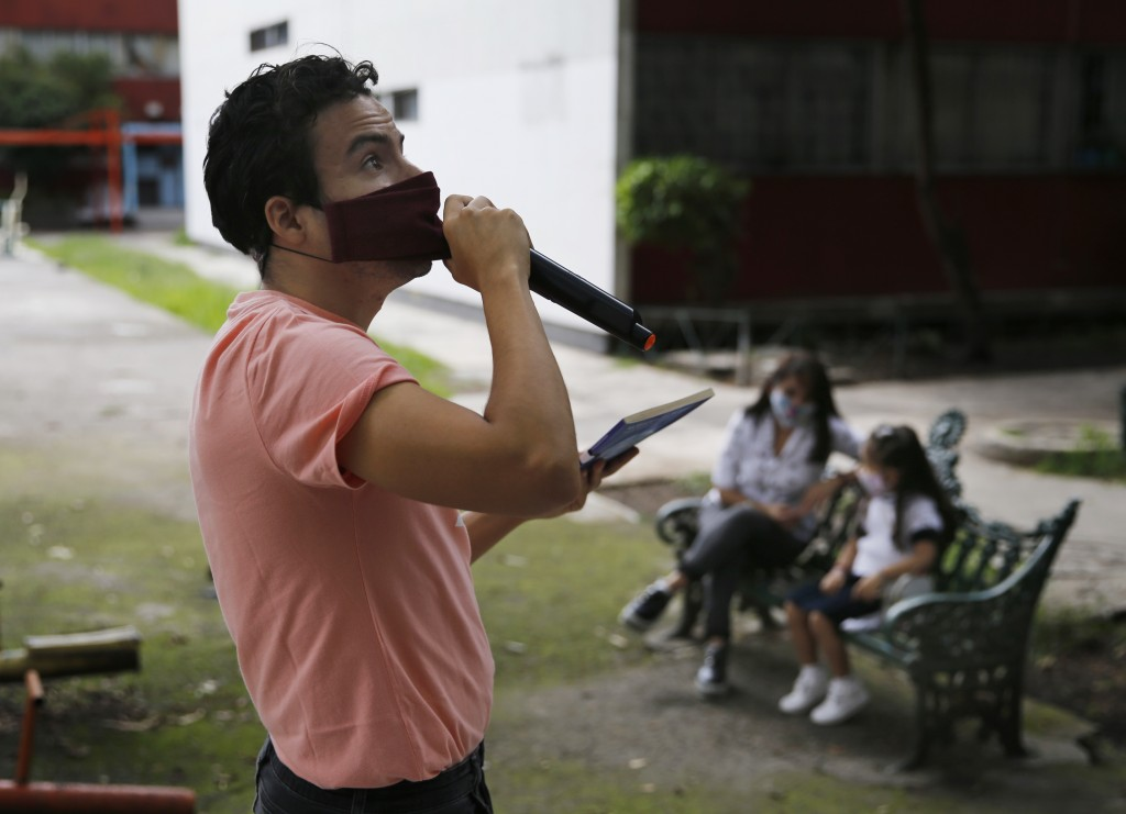 Residents listen from a bench, background, as Percibald Garcia reads children's books aloud outside the high-rise buildings in the Tlatelolco housing ...