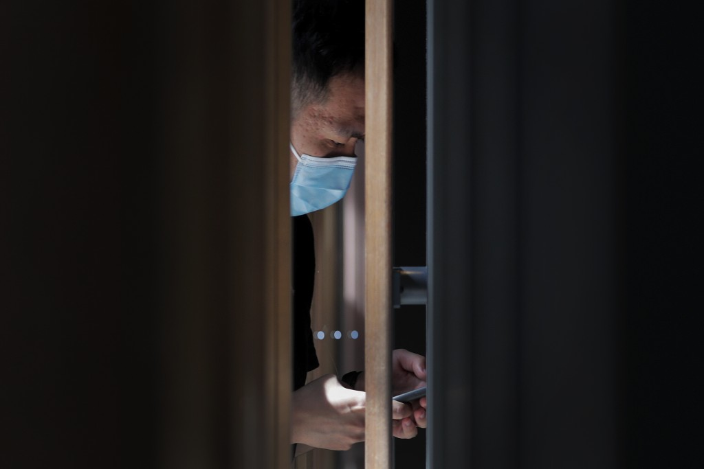 A man wearing a face mask to protect against the new coronavirus opens his health code on his smartphone before entering a cafe at a shopping district...