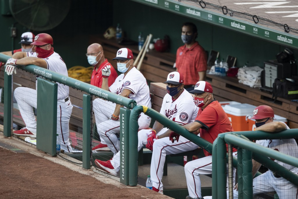 Washington Nationals manager Dave Martinez, third from right, and all the others in the dugout, wear a masks during an exhibition baseball game agains...