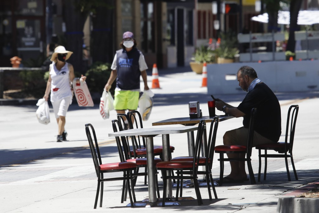 A patron sits at a table set on a street outside of a restaurant Saturday, July 18, 2020, in Burbank, Calif. The city of Burbank has closed off some s...