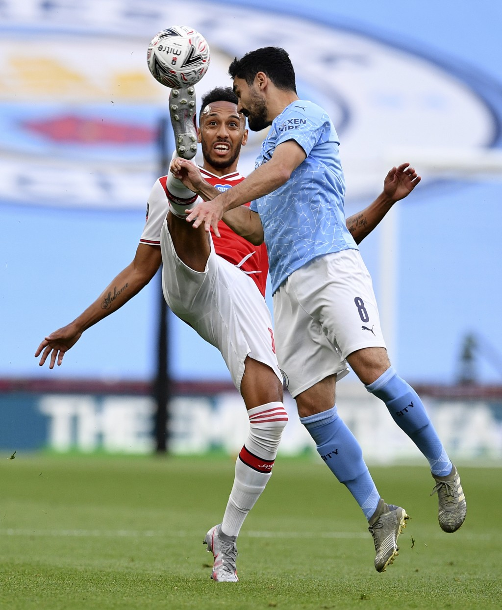 Arsenal's Pierre-Emerick Aubameyang, left, kicks the ball away from Manchester City's Ilkay Gundogan during the FA Cup semifinal soccer match between ...