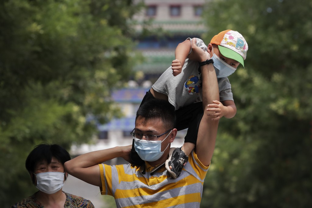 A man wearing a face mask to protect against the new coronavirus puts his masked child on his shoulders as they visit to a shopping district in Beijin...