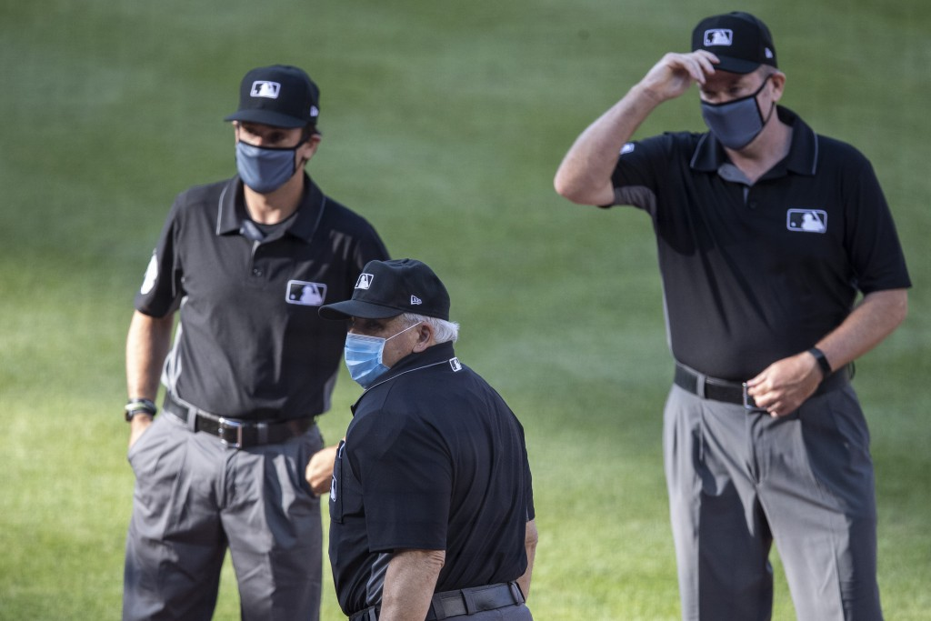 The umpires, wearing face masks, gather before an exhibition baseball game between the Washington Nationals and the Philadelphia Phillies at Nationals...