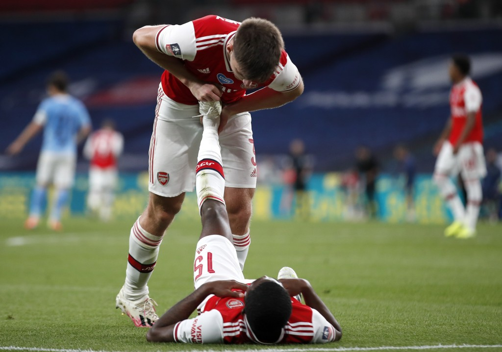 Arsenal's Kieran Tierney helps teammate Ainsley Maitland-Niles with cramp during the FA Cup semifinal soccer match between Arsenal and Manchester City...