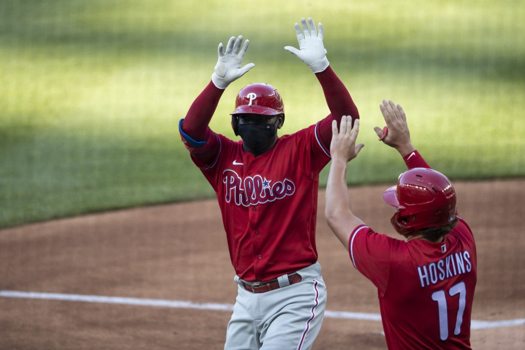 Philadelphia Phillies' Didi Gregorius celebrates without touching, while wearing a mask, his three-run homer with Rhys Hoskins during the first inning...