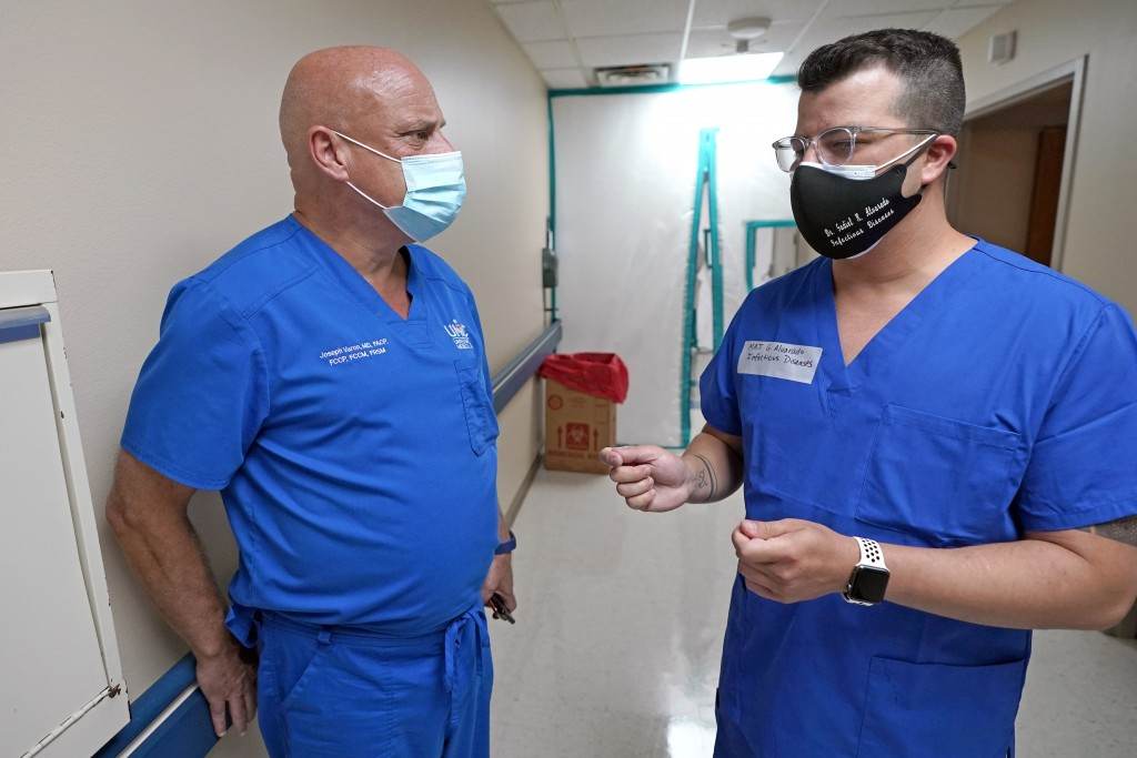 FILE - In this July 16, 2020 file photo, Infectious Disease Physician Army Maj. Gadiel Alvarado, right, with the Urban Augmentation Medical Task Force...