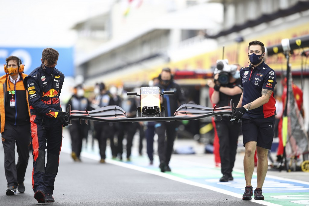 Mechanics of Red Bull driver Max Verstappen of the Netherlands carry a front car piece prior the the Hungarian Formula One Grand Prix race at the Hung...