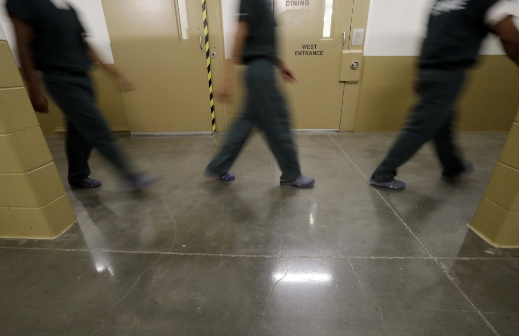 Inmates walk down a hallway at the Otay Mesa Detention Center Wednesday, Aug. 23, 2017, in San Diego. The facility was at the center of the first big ...