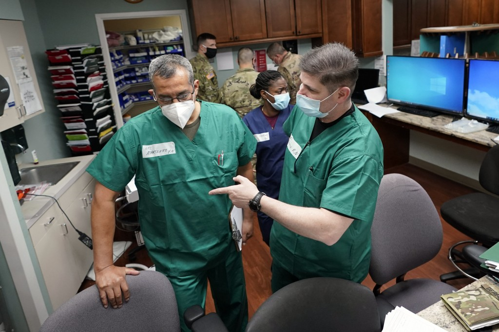 FILE - In this July 16, 2020 file photo, Registered nurses Army Lt. Col. Oswaldo Martinez, left, and Maj. Andrew Wieher, right, with the Urban Augment...
