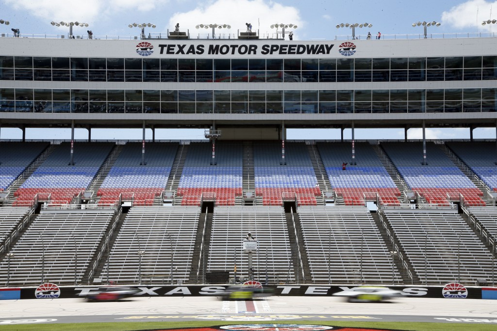 Drivers race past the start/finish line as they pass empty stands at Texas Motor Speedway during the NASCAR Xfinity auto race at in Fort Worth, Texas,...