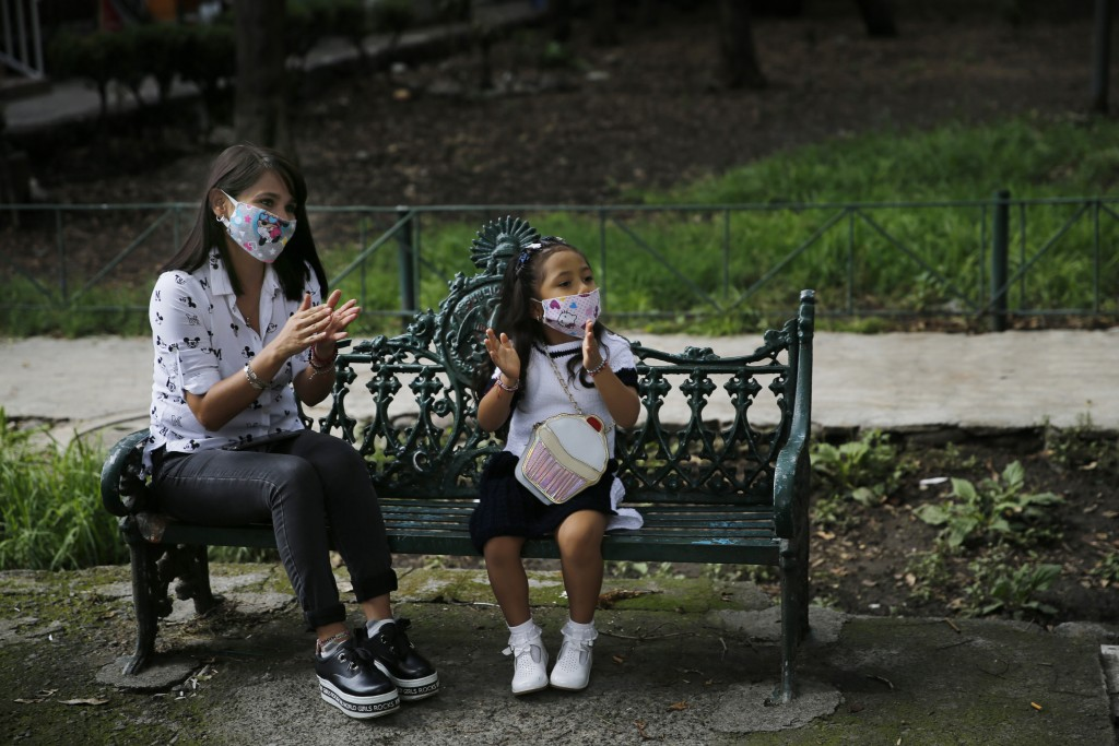 Residents clap as Percibald Garcia reads children's books aloud outside the high-rise buildings in the Tlatelolco housing complex, in Mexico City, Sat...