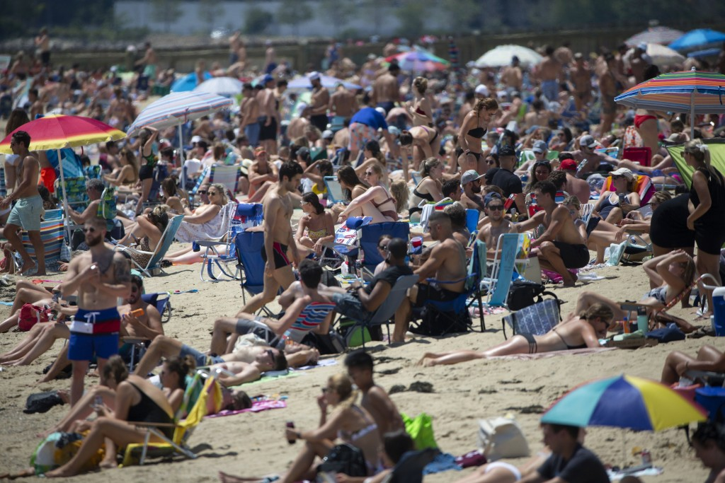 People gather on the beach, Saturday, July 18, 2020, in the South Boston neighborhood of Boston. Temperatures in the city reached into the 90's on Sat...