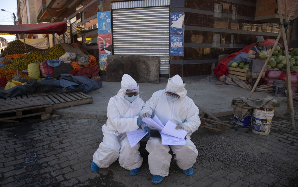 Healthcare workers dressed in full protective gear organize their documents of data they have collected during a house-to-house new coronavirus testin...