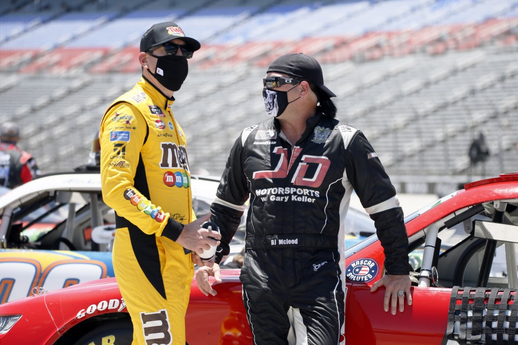 Kyle Busch, left, talks with B.J. McLeod, right, on pit road prior to the NASCAR Xfinity auto race at Texas Motor Speedway in Fort Worth, Texas, Satur...