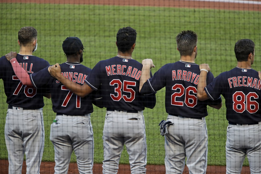 Members of the Cleveland Indians line up for the national anthem before an exhibition baseball game against the Pittsburgh Pirates in Pittsburgh, Satu...
