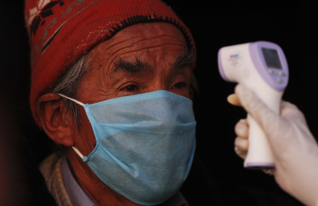 A resident stands still as a healthcare worker dressed in full protective gear measures his temperature during a new coronavirus testing drive in the ...