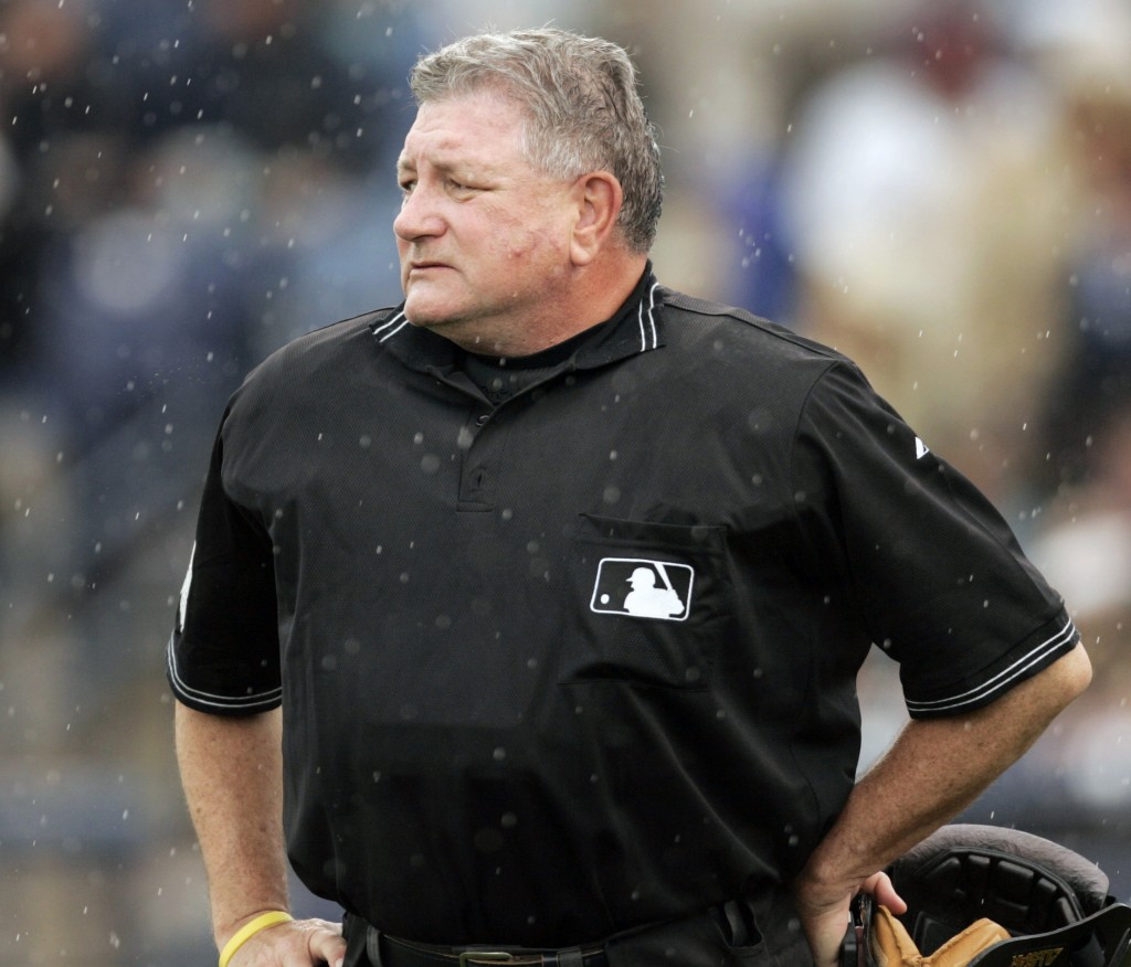 FILE - In this March 21, 2006, file photo, home plate umpire Rick Reed watches the grounds crew cover the infield during the third inning of a spring ...