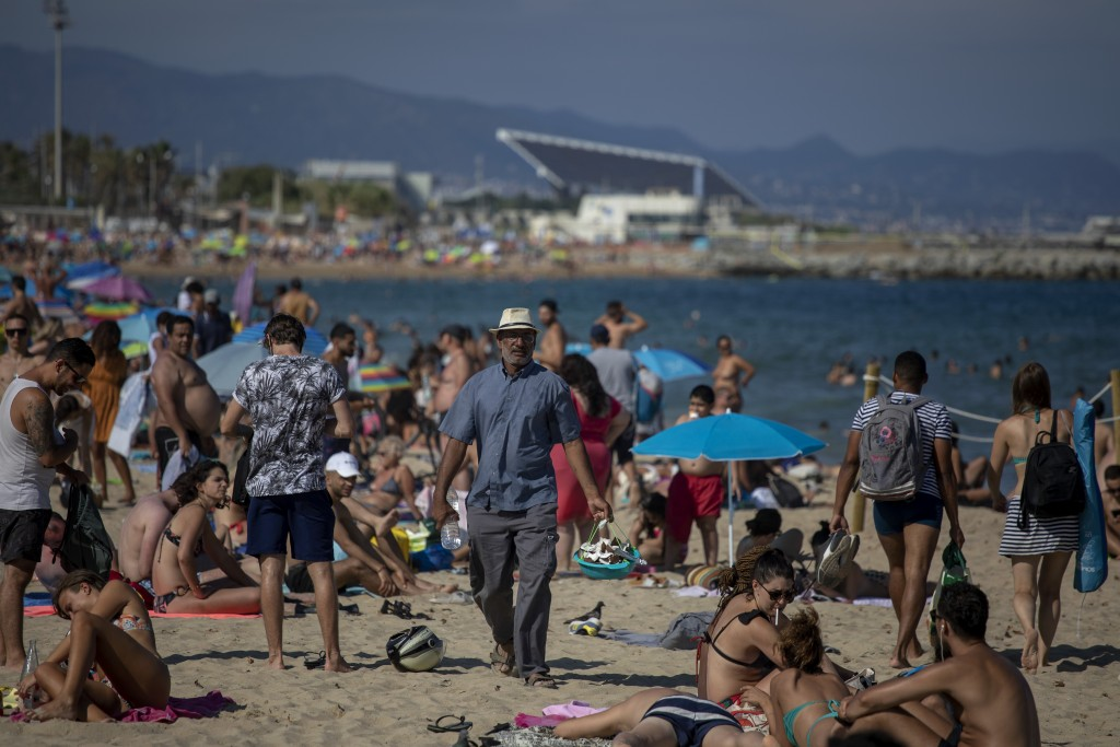 People enjoy the beach in Barcelona, Spain, Saturday, July 18, 2020. Police in Barcelona are closing access to a large area of the city's beaches due ...