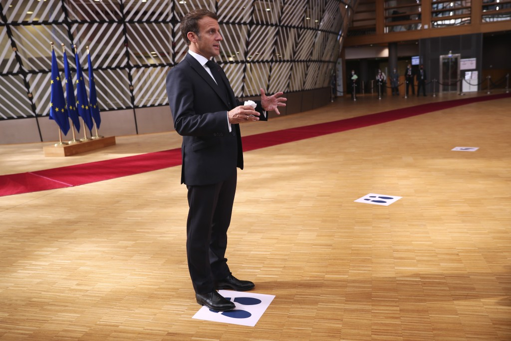French President Emmanuel Macron makes a statement to the media as he stands on a physical distancing marker on arrival for an EU summit in Brussels, ...