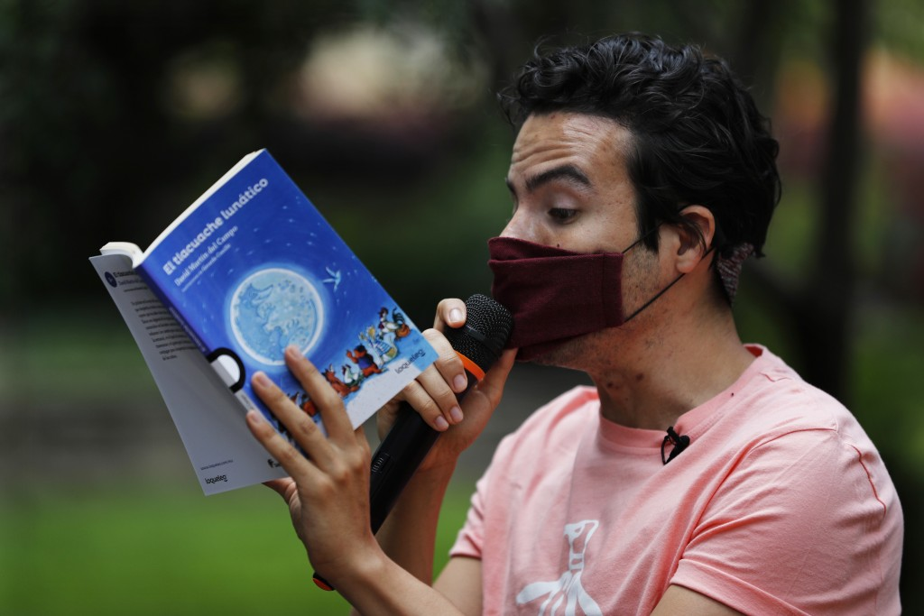 Percibald Garcia uses a microphone to read aloud children's books amid the high-rise housing complex of Tlatelolco, in Mexico City, Saturday, July 18,...