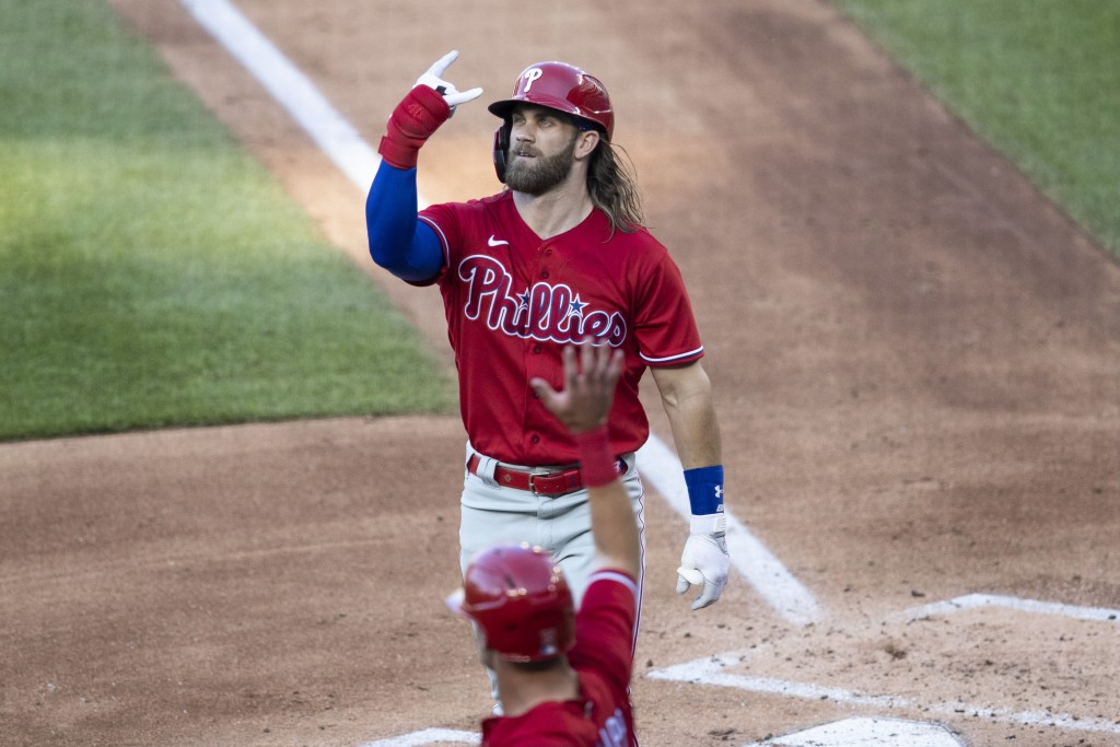 Philadelphia Phillies' Bryce Harper celebrates his three-run homer during the second inning of an exhibition baseball game against the Washington Nati...