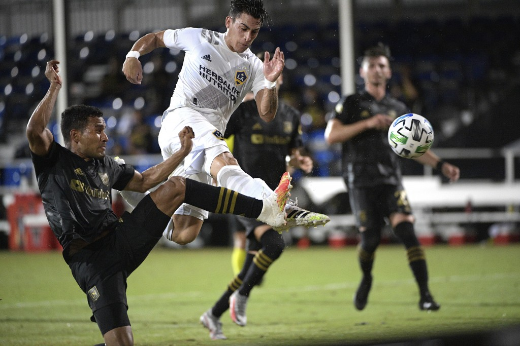 LA Galaxy forward Cristian Pavon, center, attempts to shoot on goal as Los Angeles FC defender Eddie Segura, left, defends during the first half of an...