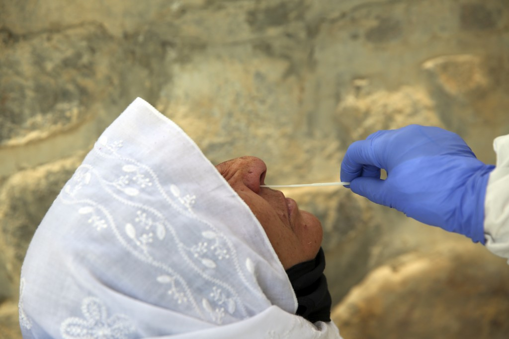 An Afghan lab technician takes a sample with a swab to test a woman for the coronavirus at the Afghan-Japan Communicable Disease Hospital ward or COVI...
