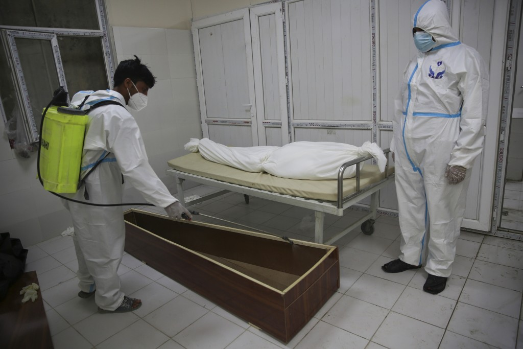Afghan health workers in protective suits spray disinfectant on the coffin of a person who died from COVID-19  at the Afghan-Japan Communicable Diseas...