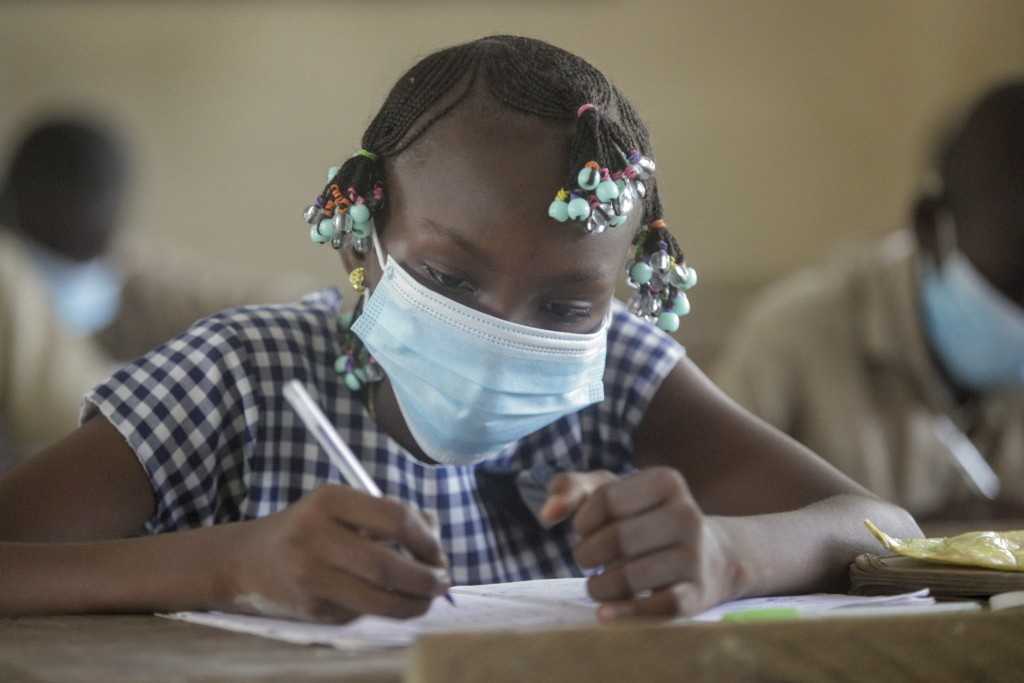 FILE - In this May 25, 2020, file photo, a student wears a mask as she attends a class at a school in the Koumassi neighborhood of Abidjan, Ivory Coas...