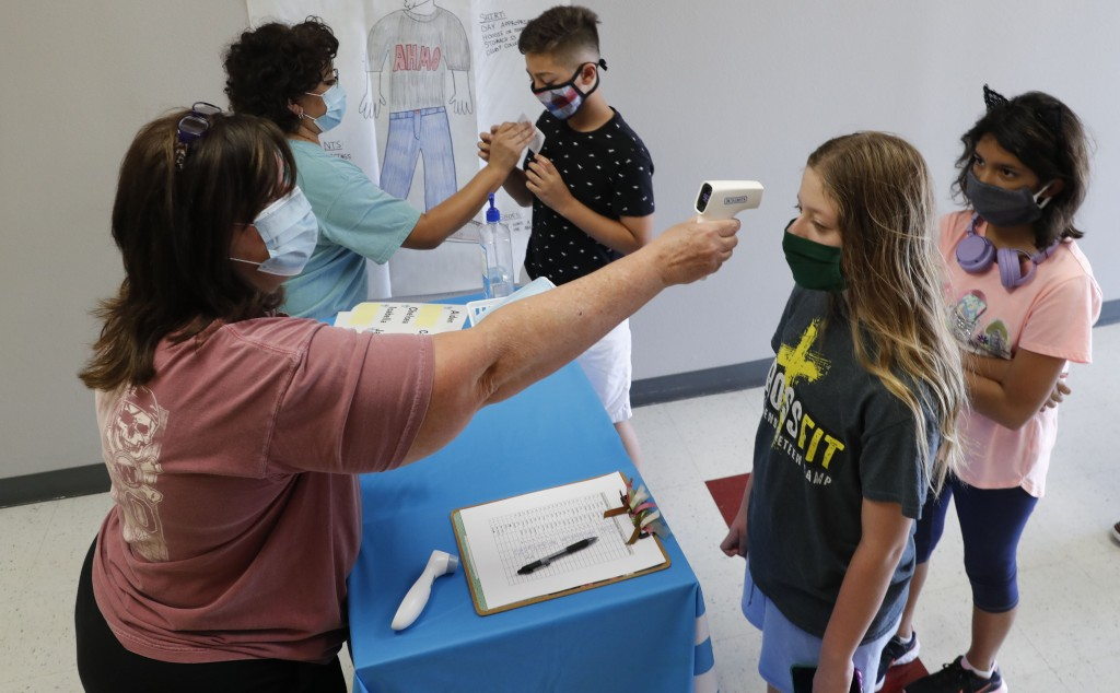 Amid concerns of the spread of COVID-19, science teachers Ann Darby, left, and Rosa Herrera check-in students before a summer STEM camp at Wylie High ...