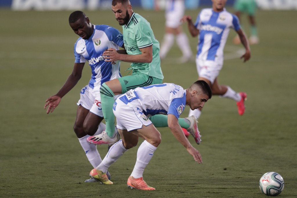 Real Madrid's Karim Benzema, centre, is stopped by Leganes' Miguel Angel Guerrero, left and Ibrahim Amadou, right, during the Spanish La Liga soccer m...