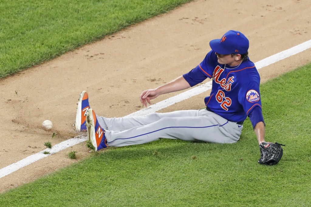 New York Mets relief pitcher Drew Smith (62) slips on the grass trying to reach an infield grounder hit by Thairo Estrada during the sixth inning of a...