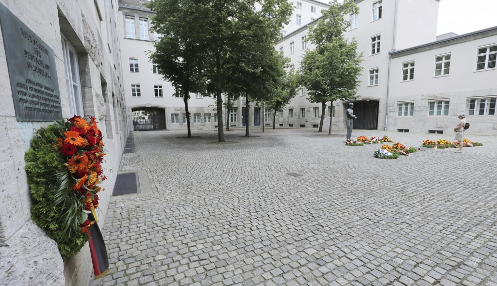 A woman stands in the Bendlerblock at the German Resistance Memorial Center and looks at wreaths and flower arrangements laid down on the 76th anniver...