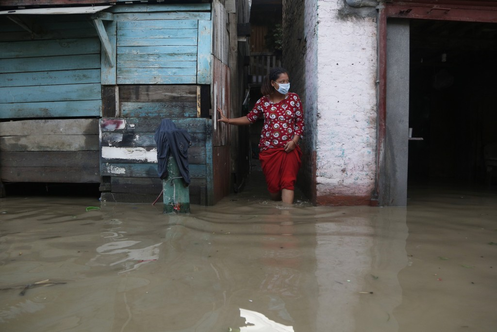 A Nepalese woman wearing a mask as a precaution against the coronavirus stands outside her flooded house on the bank of Bagmati river following heavy ...
