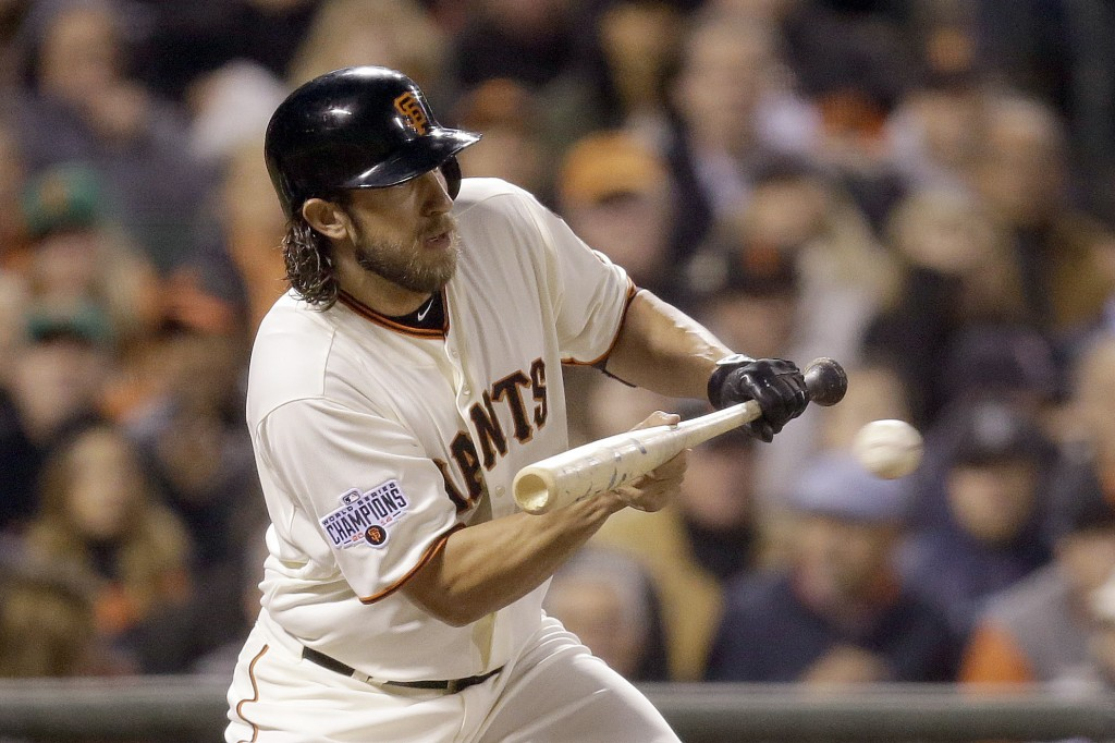 FILE - In this  Wednesday, April 22, 2015 file photo, San Francisco Giants' Madison Bumgarner bunts on a pitch from Los Angeles Dodgers' Clayton Kersh...