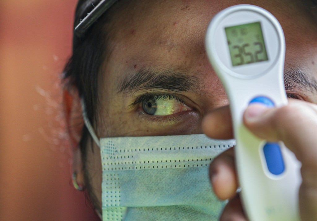 A worker measures the temperature of a man before allowing him to enter La Vega market to curb the spread of COVID-19 in Santiago, Chile, July Sunday,...