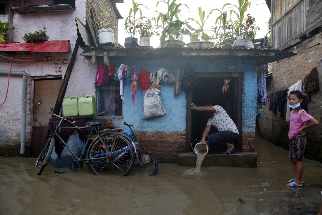 A Nepalese man clears flood water from his house on the bank of Bagmati river following heavy monsoon rains in Kathmandu, Nepal, Monday, July 20, 2020...