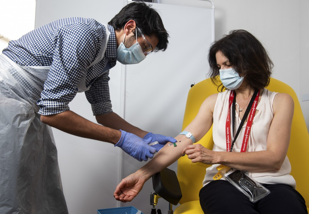 In this handout photo released by the University of Oxford a doctor takes blood samples for use in a coronavirus vaccine trial in Oxford, England, Thu...