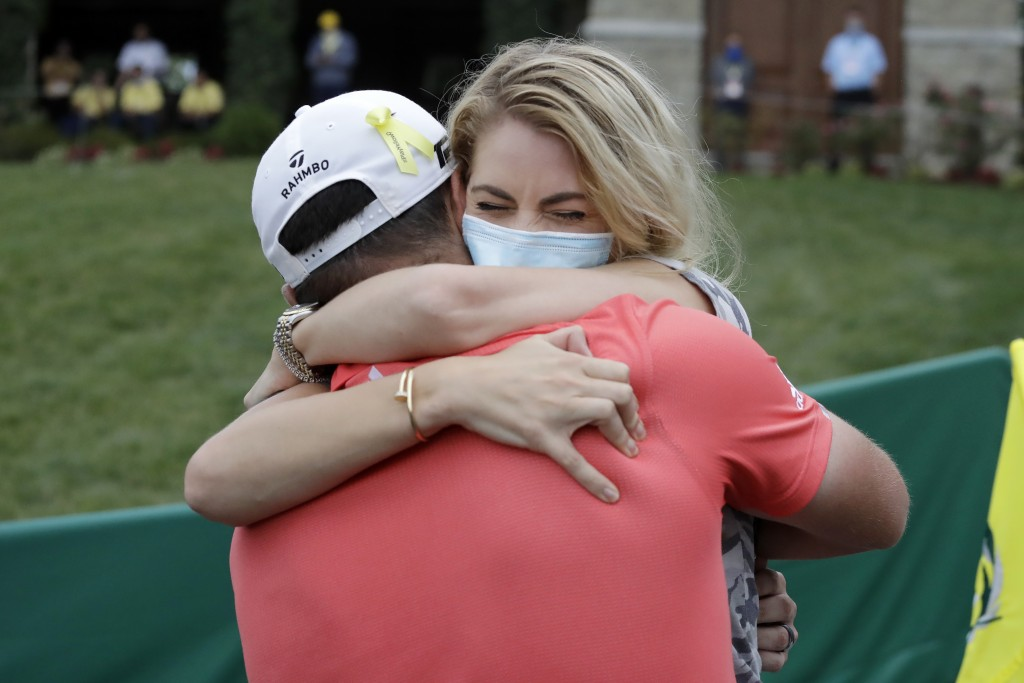 Jon Rahm, of Spain, left, celebrates with his wife, Kelley Cahill, after winning the Memorial golf tournament, Sunday, July 19, 2020, in Dublin, Ohio....