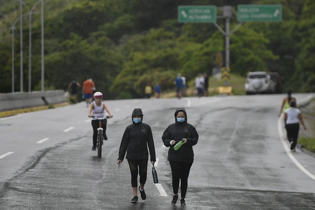Women wearing masks to curb the spread of the new coronavirus exercise along Boyaca Avenue in Caracas, Venezuela, Sunday, July 19, 2020. (AP Photo/Mat...