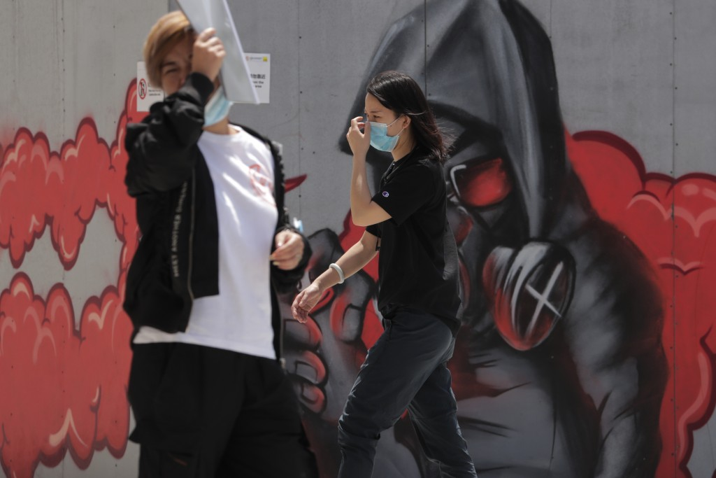 A woman adjusts her face mask as she walks by a graffiti artwork on display outside a mall in Beijing, Monday, July 20, 2020. China's latest coronavir...