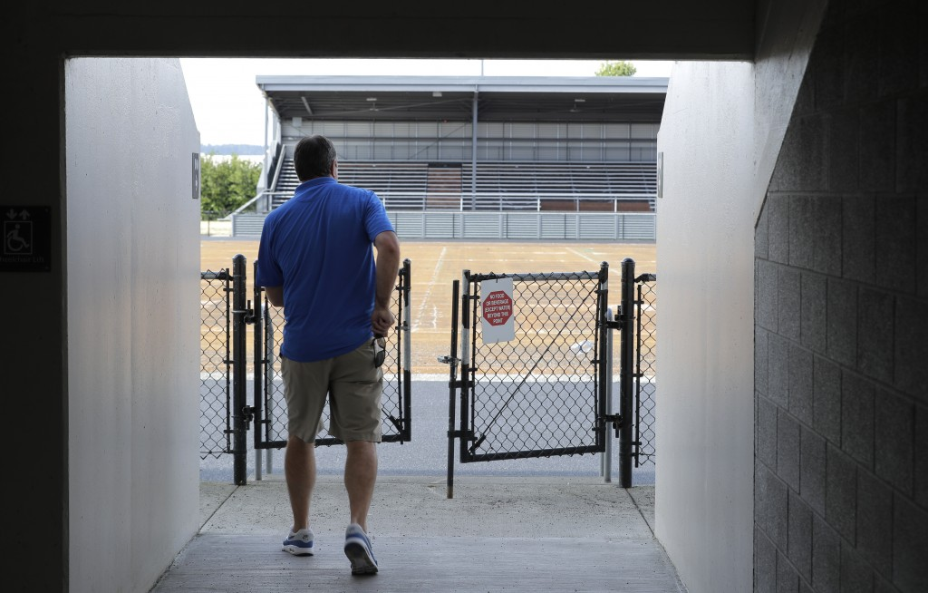 Mick Hoffman, executive director of the Washington Interscholastic Activities Association, walks toward a field gate, Thursday, July 16, 2020, near em...