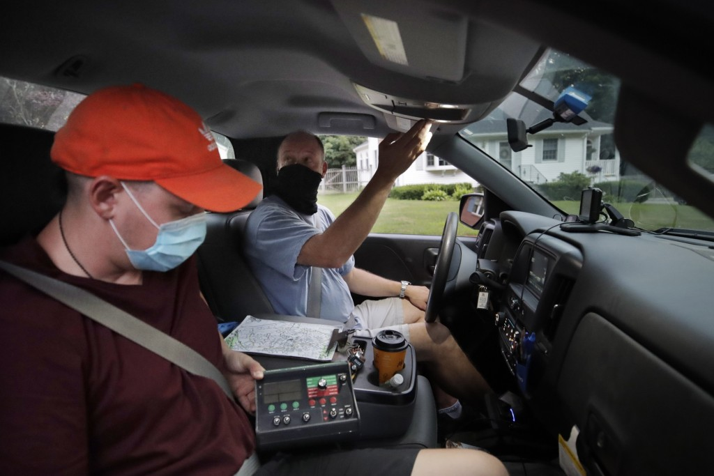 Chris Gagnon, center, field operations manager for the East Middlesex Mosquito Control Project, prepares to spray to control mosquitos from a pick-up ...